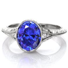 A flared, mil-grained knife-edge band gives Design 4002 an unmistakable vintage inspiration. The 2.00 carat lustrous oval-cut center blue sapphire is bezel set and framed by two diamonds on either side. The band is further detailed with hand formed filigree, micro pavé diamonds and hand engraving.
