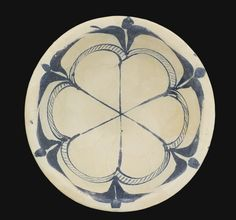 An Abbasid tin-glazed pottery bowl, Iraq, 9th/10th century the rounded body with everted rim and short foot, decorated in cobalt blue in an opacified tin glaze with a central six-petalled rosette with hatched border sprouting stylised palmettes  20.6cm. diam.