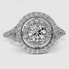the embodiment of glamour,  a round center diamond encircled by two pavé-set diamond halos and an split-shank diamond band~