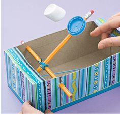 This tissue box catapult toy craft shoots marshmallows. Materials: family-sized tissue box scissors 2 unsharpened pencils rubber b...