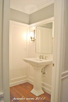 Powder room. like the white mouldings with most of the wall painted white then trimming in blue. clean and crisp