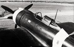 Close-up view of the front half of the fuselage of a Re.2000 Falco I fighter of the Italian 74th Squadron at rest at an airfield, date unknown