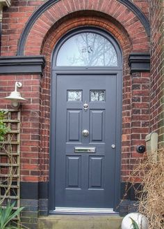 A striking, slate grey-coloured double-glazed door with chrome trim, handle, knocker and letterbox, and semi-circular frosted window above. Installed in a vintage red brick house with traditional wall light.