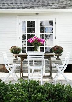 Love the white chairs against the weathered table - the elegant simplicity of the entire space