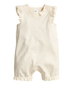 CONSCIOUS. Sleeveless jumpsuit in organic cotton jersey with a printed pattern. Decorative ruffle trim at armholes and hems, small bow at neckline, and concealed snap fasteners at shoulders, sides, and gusset.