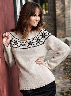 Med rundt bærestykke forskønnet med sort mønsterbort får den naturfarvede sweater et enkelt look