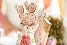 Розового цвета ваза, украшенная рисунком розы, с леденцами в форме