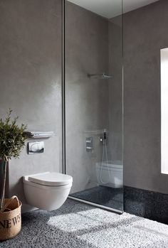 Another pebble floor, this one with a not-tiled wall, which lets the space feel much softer. It's in Italy and there aren't details about the wall surface. The step-down tub is intriguing too (hard to tell if it's comfy?).