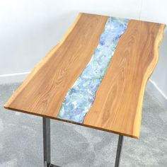 Unique new design, handmade by British Craftsmen made natural edge English Elmd ining or conference table,with a Resin Art panel running the length of the top. The resin art panel is hand poured in a selection of colours (almost any colours/combination available) for a natural, organic effect so no two pieces are alike. Makes an excellent conference table as the art can be poured in company colours -CNC routed logo also possible. Sat on clear acrylic perspex legs, although steel legs ar...