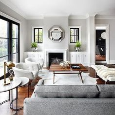 The Design Company - living rooms - gray walls, gray wall color, hardwood floors, marble fireplace, marble fireplace surround, white cabinets, white cabinetry, white built-in cabinets, fireplace cabinets, fireplace built-ins, ring pull hardware, cabinets flanking fireplace, nickel ring pull hardware, silver bowl, silver pedestal bowl, square shaped window, windows next to fireplace, windows flanking fireplace, windows either side of fireplace, octagon mirror, mirror over fireplace, mirror…