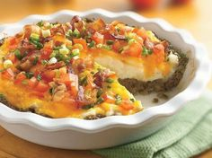 Ground Beef and Twice-Baked Potato Pie    1 lb lean (at least 80%) ground beef  1/4 cup chopped onion  1/4 cup plain bread crumbs  1/2 teaspoon dried sage leaves  1/2 teaspoon salt  1 egg  1 package (1 lb 8 oz) refrigerated garlic mashed potatoes (or your own recipe  1 cup shredded Cheddar cheese (4 oz)  1/4 cup chopped fresh tomato, if desired  2 slices precooked bacon, chopped, if desired  2 medium green onions, chopped (2 tablespoons), if desired    Heat oven to 350°F.