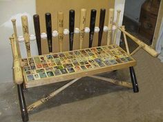 A bench made out of bats, balls and baseball cards! Very creative! perfect for a Chiefs themed basement!