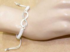 Magnifique bracelet réglable blanc émail et strass sur cordon coton tressés modèle signe infini. Frais de port offert. Quantités limitées, profitez en vite