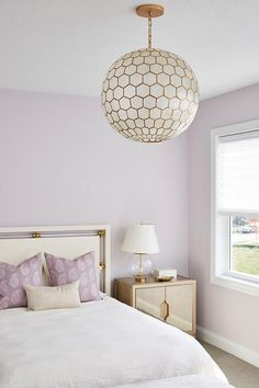 A capiz globe chandelier lights a stunning purple and gold bedroom boasting soft purple painted walls and a white and gold headboard positioned behind a bed dressed in white bedding accented with purple paisley pillows.