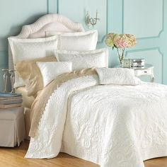 Matte lasse coverlet mixed with mocha colored sheets and a Tiffany blue wall!