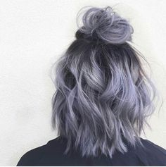 Lavender shoulder length hair in a half up half down bun with light curls
