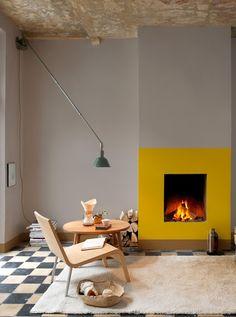 jaune de la cheminée qui rappelle le feu, crée chaleur et lumière dans un espace plutôt froid par les murs et le carrelage, invite à s'asseoir, côté contemporain avec une certaine épuration de déco