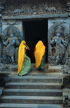 Two women climb the steps of the Hoysaleswara Temple in southern India. Photograph by George Puvvada