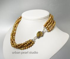 Stunning designer one of a kind gold multi strand pearl necklace with a focal of an ammonite fossil nautilus shell clasp in 925 sterling silver. Description from etsy.com. I searched for this on bing.com/images