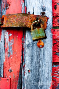 Old door locked with a padlock with a rusty key still sticking in it