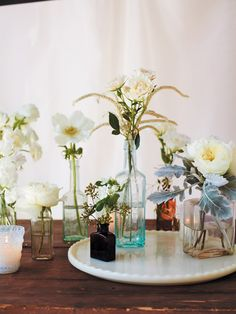simple white flower centerpieces in eclectic glass bottles | matthew robbines design