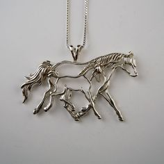 Mare and Foal Pendant Necklace in Sterling Silver. The mare and foal necklace shows how a foal will stride out with their Mom, keeping pace. The foal will not be left behind. Designed as a line drawin