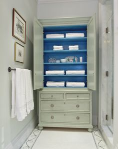 detail: cabinet used as bath storage, doors left open, painted a beautiful blue inside and kept pretty with crisp white towels and a few trinkets