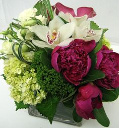 This is a cube vase floral arrangement that features peonies, cymbidium orchids and hydrangea in a hot pink, white and green color scheme and lily grass loops.  See our entire selection at www.starflor.com.  To purchase any of our floral selections, as gifts or décor, please call us at 800.520.8999 or visit our e-commerce portal at www.Starbrightnyc.com. This composition of flowers is generally available for same day delivery in New York City (NYC). SQ131