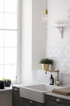 white kitchen with grey cabinets and brass details