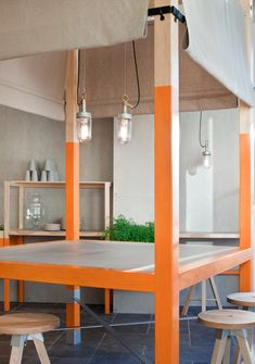 The structure in the centre of the space is used as a dining table. Beige canvas blinds around the sides aim to make the otherwise open four...