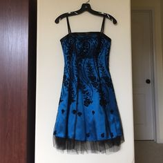 Bright Blue Mini Prom Dress. Brand: Morgan & Co. Size: 0. Worn once for prom. Great for prom and parties.  Beautiful cross back ribbon with zipper in the back. Black velvet rose pattern running throughout the dress with lace undercoat. Morgan & Co. Dresses Prom