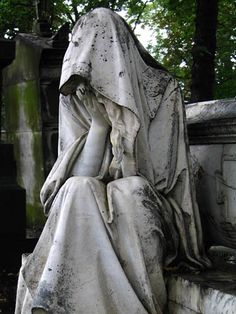 This is how Donnie is seen through the eyes of his beloved family members. They all mourn for the loss of him. Here, an aged statue is sitting down with her hands to her face. She is completely covered in clothing and is showing sad emotion. It is a beautiful setting because the statue is the main focus which helps draw attention to the centre of the image.