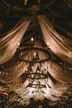 Fabric, branches, twinkle lights and moss on wagon wheel chandeliers in the Carriage House of Magnolia Plantation. #chs #weddings @jeannemitchum