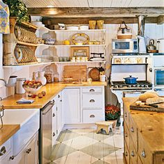 Charming and Cheery   Original wood floors dressed up with a coat of paint add elegance to this cozy cottage kitchen. A refurbished English dresser-turned-island plays up the historic character; open shelving displays a mix of pottery for a punch of color.      CoastalLiving.com