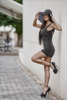 Leggy model propped against wall in bodycon dress and ankle strap high heels