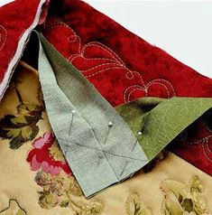 """Open the tails. With right sides together, place one on top of the other at a right angle. Join the strips with a diagonal seam. Before stitching, check to be sure the strips are not twisted. Trim the seam allowance to 1/4"""" and finger-press open."""