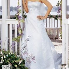 NWT David's Bridal Wedding Dress.  NWT David's Bridal White Dress with Rose Wedding Dress. Size 14. It's BRAND NEW with tags. It's in great condition! ‼️ NO TRADES NO PP‼️ WELCOME TO MAKE AN OFFER! ❌⭕️ David's Bridal Dresses Strapless