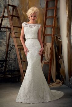 Brides.com: Wedding Dresses We Love, For Under $1,000. A high neckline looks especially elegant on a smaller chest.  Lace fit-and-flare wedding dress with beaded belt, $900, Mori Lee by Madeline Gardner  See more Mori Lee wedding dresses.
