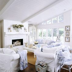 I love this cozy beach cottage living room! The white paneling gives the lofty space a crisp, cottage feel. I also really like the wood mantel with shell carvings that frame the marble fireplace. I would add in some pops of color with some yellow and bright blue pillows for the white sofas. #BHG