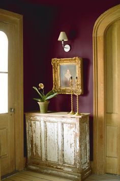 A rustic-finished sideboard and trim appear more refined when paired with gold accessories and deep, wine-colored walls. | New London Burgundy