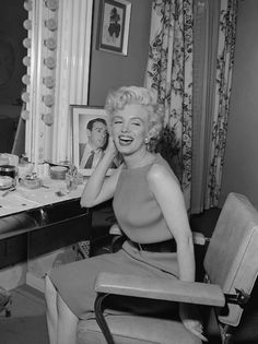 Marilyn Monroe af her Fox dressing room where she was going to give a press conference. I love the photo of Joe behind her!