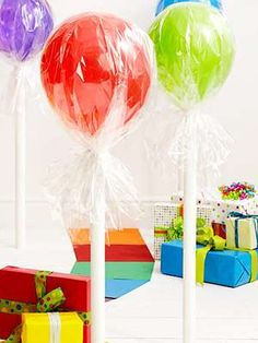 To make the jumbo lollipops you will need some colorful balloons, wrapping paper tubes, paint, and some clear cellophane. Simply paint the paper tubes in white, and then assemble the balloon on top, and wrap it up with the cellophane, and lastly, tie it up. The finished product is truly surreal.     To add even more goodies to the party you can make individual candies by taking two colored plastic dinner plates and taping them together, and then wrapping them in the cellophane.