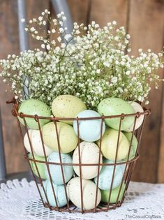 Such a simple but beautiful Farmhouse Easter vignette-pastel colored Easter eggs with baby's' breath in rusty wire basket.
