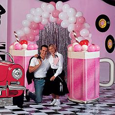 """This arch is the coolest photo setting for your sock hop! The striped straws and silver corrugated mugs tempt you to taste the frosty """"soda"""" made of pink and white balloons."""