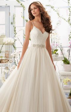 Be royalty for your long awaited day in Blu by Mori Lee 5416. This wedding gown offers a flattering V-neckline with satin shoulder straps leading the low V-back. Soft net, ball skirt runs down the ground leading an impressive train. Removable beaded satin belt included.