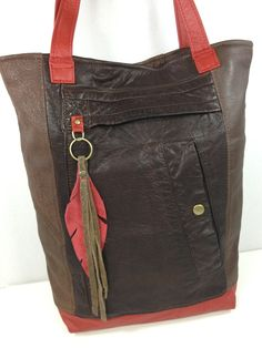 ;I actually used parts of three different leather jackets to make this buttery soft bag. Inside is lined with a beautifully coordinated upholstery weight fabric. One zippered pocket and two open pockets inside. All hardware is antique bronze in color. Feather and tassel attaches to the bag on a key ring.