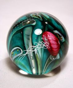"A creation from the GlassMasters at the Glass Eye Studio. Phantom of the Sea, a Jellyfish paperweight,  from the Environmental Series. Signed and presented with storycard and velvet keepsake box.  Approximately 3.0"" diameter."