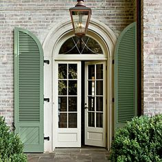 """Everything was done to give the house some height because the homes on either side loom over it,"""" says Jeremy. """"We tried to pick it up a bit."""" Paul and Jeremy created an oversize but not imposing 9-foot-tall limestone entryway. Light spills into the foyer through the 7-foot French doors and leaded-glass transom. A pair of Palladian-style shutters adds a single punch of color (Pratt & Lambert's Artichoke). A bell-shaped front lawn furthers the illusion of more height."""