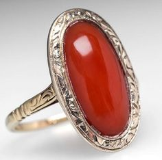 This beautiful antique red coral ring features a natural cabochon surrounded by an ornately etched white gold bezel. The shank of the ring is also decorated with etched designs. This ring is crafted of solid 14k yellow and white gold