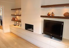 Modern version of our hearth… Not exactly what I'm thinking. Plasma storage and AV unit in lacquer and limestone.